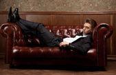 Un homme en costume couché sur le canapé — Photo