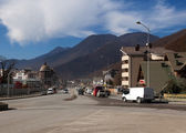Road and the city on the background of sky and mountains — Stock Photo