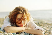 Beautiful young woman lying on the beach — Stock Photo