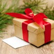 Beige gift box with red ribbon in soft focus — Stock Photo