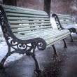 Bench in winter and falling snow, soft focus — Stock Photo