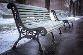 Bench in winter and falling snow, soft focus — Zdjęcie stockowe