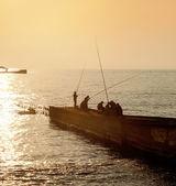 рыбаки на пирсе на фоне заката — Стоковое фото
