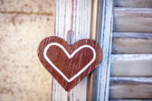 Wooden heart on a background of blue shutters — Stock Photo