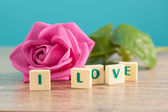 The word love and pink roses — Stock Photo