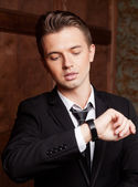 Attractive young businessman looking at his watch — Stock Photo