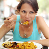 Young woman eating paella in a cafe — Stock Photo