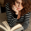 Young woman reading a book lying on the carpet, in soft focus — Stock Photo