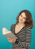 Portrait of a young woman with a book on a blue background — Stock Photo