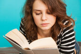 Young woman reading a book lying, in soft focus — Stock Photo