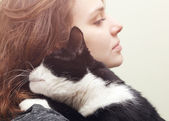 Beautiful young woman  with monochrome black and white cat — Stock Photo