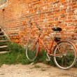 Old bicycle on the background of red brick walls — Stock Photo #41733327