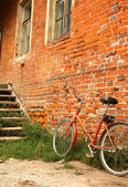 Old bicycle on the background of red brick walls — Foto de Stock
