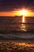 Playa en puesta de sol y nave de fondo, la imagen defocused — Foto de Stock