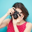 Beautiful girl with vintage photo camera on a blue background in — Stock Photo #42329683