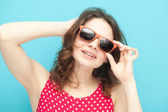 Beautiful girl in sunglasses on a blue background in soft focus — Foto Stock