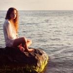 Girl sitting on a rock sea — Stock Photo #42827081