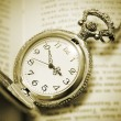 Vintage pocket watch lying on the book, retro style — Stock Photo #43515739