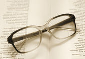 Reading glasses lying on an open book, retro styled image — Photo