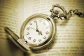 Vintage pocket watch lying on the book, retro style — Stock Photo