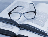 Glasses and open books on the table — Stock Photo