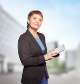 Attractive woman 50 years old with a tablet in hands — Stock Photo