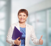 Attractive woman 50 years old with a folder for documents — Stock Photo