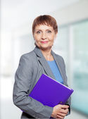 Attractive woman 50 years old with a folder for documents — Stockfoto