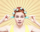 Grappige portret van roodharige meisje in haar krulspelden op retro backg — Stockfoto