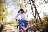Beautiful young woman with mountain bicycle — Stock Photo