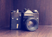 Retro camera on the shelf in the closet, instagram retro effect — Stock Photo
