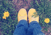 Yellow sneakers on green grass — Stock Photo
