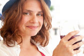 Beautiful girl in a hat drinking sangria — Stock Photo
