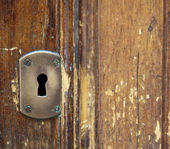 Retro keyhole on a wooden door — Stock Photo