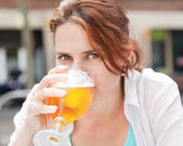 Pretty girl drinking beer from the glass in a cafe — Stock Photo
