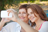 Mother and adult daughter are doing selfie on phone — Stock Photo