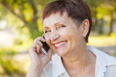 Beautiful woman of 50 years with a mobile phone outdoors — Stock Photo