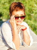 Beautiful woman 50 years in sunglasses, Outdoors — Stock Photo