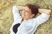 Beautiful woman 50 years on haystack, Outdoors — Stock Photo