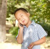 Funny asian boy with a mobile phone in a park — Stok fotoğraf