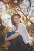 Beautiful girl sitting in the glow of the setting sun, in soft focus — Stock Photo