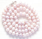 String of pearls delicate pink color, in soft focus, with highli — Stock Photo