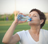 Attractive woman 50 years old, drinking water after fitness — Stock Photo