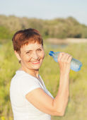 Sports woman  50 years with a  bottle of water, outdoors — Foto Stock