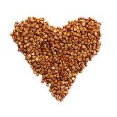 Heart shaped brown buckwheat, valentine heart of brown groats. I — Stock Photo
