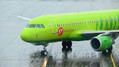 MOSCOW - SEPTEMBER 6: S7 Airlines A319 in Domodedovo Int., Moscow on September 6, 2013. S7 Airlines green-colored aircraft with enabled taxi lights follows the yellow marking to airport terminals. — Stock Photo