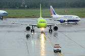 MOSCOW - SEPTEMBER 6: S7 Airlines A319 and Transaero B737 in Domodedovo International, Moscow on September 6, 2013. S7 and Transaero aircrafts follows the yellow marking to airport terminals. — Stock Photo