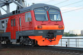 VORONEZH - MAY 12: Russian Railways commuter electric train passes bridge in Voronezh on May 12, 2013. Electric train ED9M route Voronezh - Liski passes steel bridge at the Voronezh reservoir. — Stock Photo