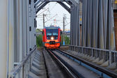 VORONEZH - MAY 12: Russian Railways commuter diesel-electric train passes bridge in Voronezh on May 12, 2013. Rail bus route to Voronezh central station passes steel bridge at the Voronezh reservoir. — Stock Photo