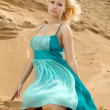 Beautiful fashionable model on the beach in beautiful dress — Stock Photo